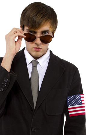govt: American spy waring a black suit and american flag armband Stock Photo