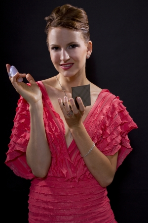 young caucasian woman applying foundation make up with a pad  isolated on a black background