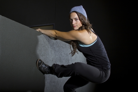 fleeing: free runner scaling or climbing a wall at night to do parkour Stock Photo