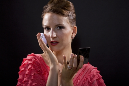 young caucasian woman applying foundation make up with a pad  isolated on a black background photo