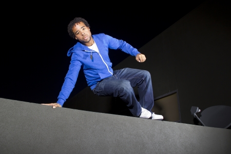 fleeing: free runner doing parkour at night on a rooftop