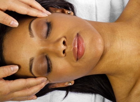 african american spa: young black female getting a head massage   facial  Stock Photo