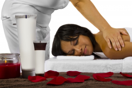 spa products on foreground, masseuse and patient on background photo