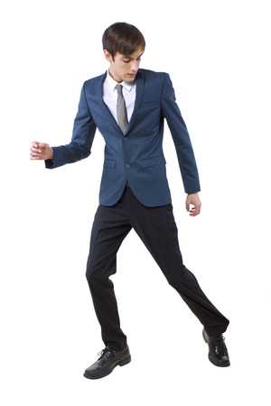 young businessman held back by imaginary obstacle pulling on leg
