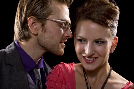 whispering couple on black background photo
