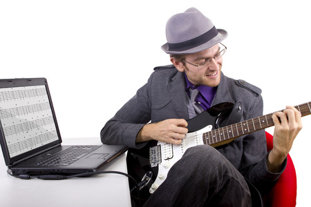 Guitarist looking at tablature online. Stock Photo