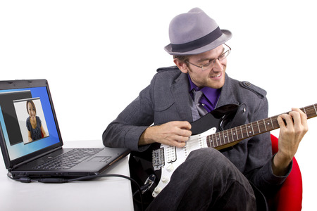 serenading: Male serenading woman online by playing a guitar on a webcam chat.