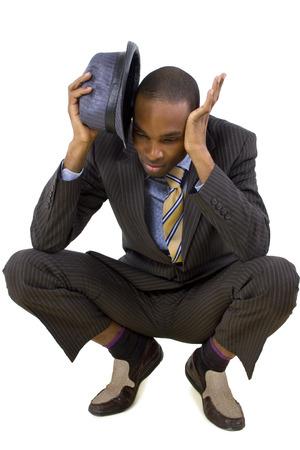 agachado: joven empresario negro agachándose de la amenaza invisible