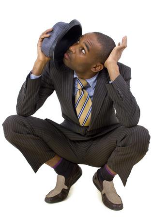 agachado: joven empresario negro agach�ndose de la amenaza invisible