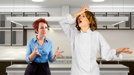 young waitress and chef fighting in a kitchen  photo