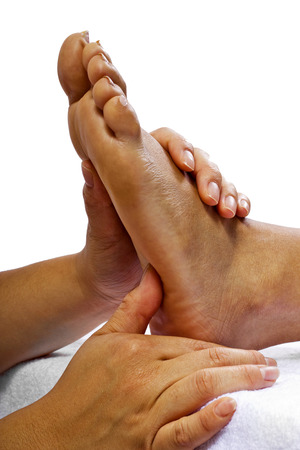 close up of masseuse massaging clients foot photo