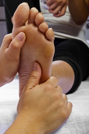 close up of masseuse massaging client's foot Stock Photo - 25282848