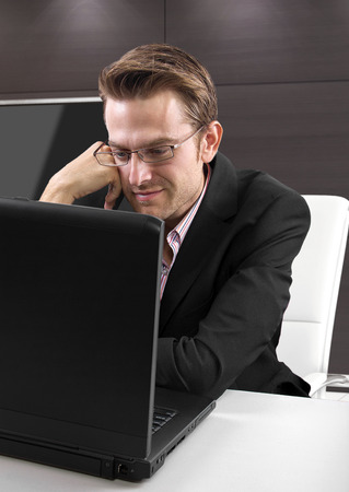 Caucasian male on a laptop computer in an office