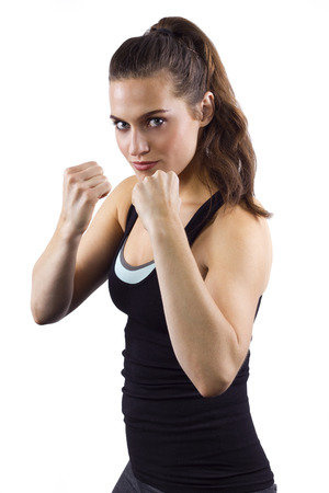 young woman in fighting stance on white