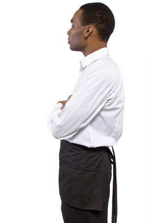 hospitality staff: young African-American waiter wearing an apron on white background