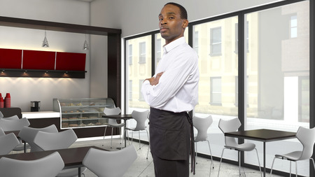 hospitality staff: young African-American waiter working in a coffee shop