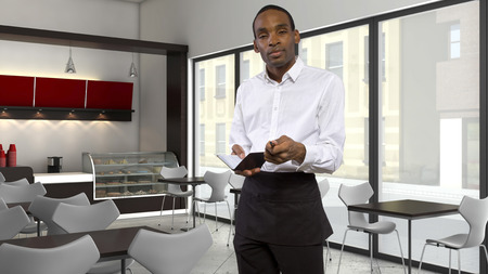 unfriendly: tired young African-American waiter in a coffeeshop Stock Photo