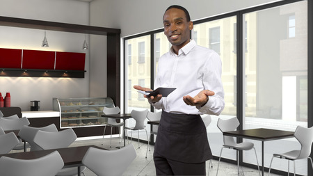 hospitality staff: tired young African-American waiter in a coffeeshop Stock Photo