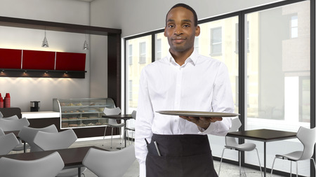 hospitality staff: young black waiter holding an empty tray in a coffeeshop