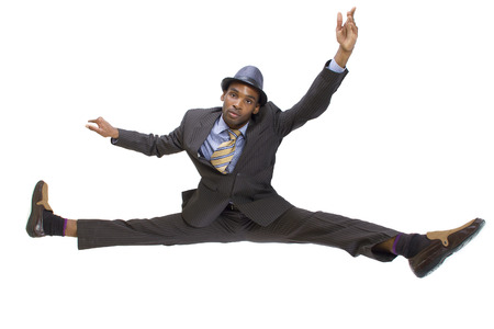 athletic black man in a suit doing the splits Фото со стока