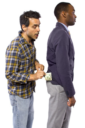 looting: sneaky man stealing cash from a victim Stock Photo