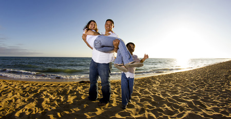 young parents with a male child at the beach photo