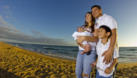 young parents with a baby and kid at the beach