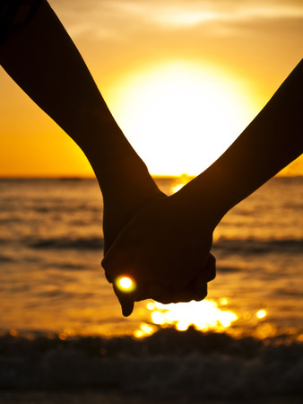 couple holding hands: couple at the beach silhouette Stock Photo