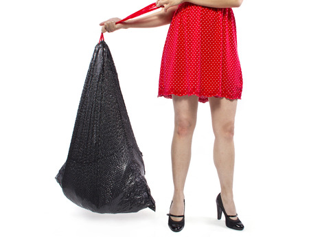 woman cleaning up and holding a black trashbag photo