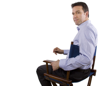 folding chair: male casting director sitting on a folding chair Stock Photo