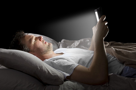 male in bed browsing the internet late at night with a tablet photo