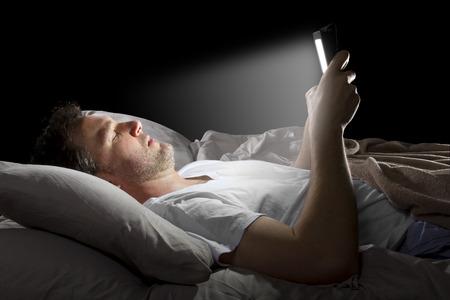 man in bed surfen op het internet 's avonds laat met een tablet Stockfoto