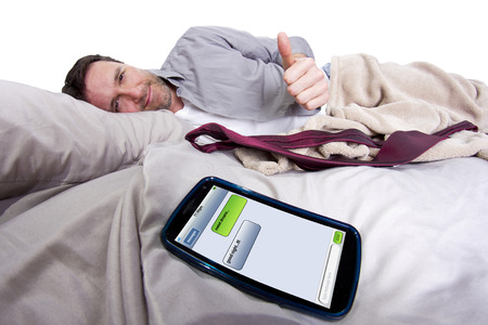 cell phone screen showing text messages while male is in bed photo