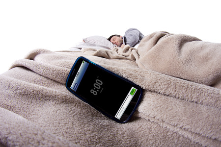 snoozing: alarm clock on a digital cell phone display with man in bed Stock Photo