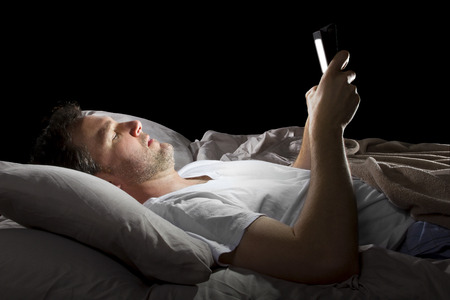 nightime: male in bed browsing the internet late at night with a tablet
