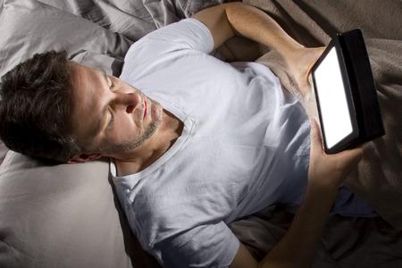 working at home: masculino en cama navegar por Internet a altas horas de la noche con una tableta Foto de archivo