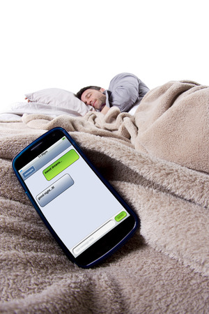 cell phone screen showing text messages while male is in bed Фото со стока - 28252849