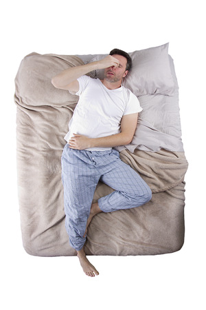 sleep: top view of sleep deprived man on a bed