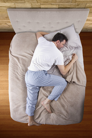 top view of bedroom with insomniac man unable to sleep photo