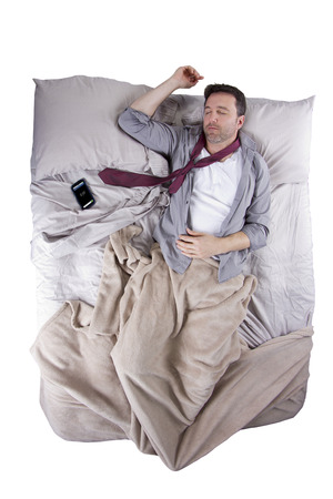 businessman sleeping in his work clothes with cellphone alarm clock photo