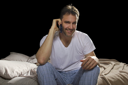 man in bedroom using cell phone late at night  photo