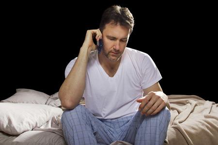 llamando: hombre en dormitorio usando el teléfono celular a altas horas de la noche