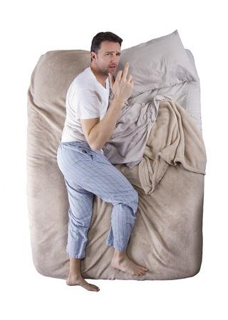 megfosztott: felülnézeti kialvatlan férfi egy ágyban Stock fotó