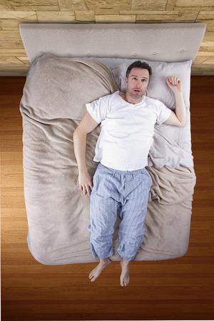 sleep: top view of bedroom with insomniac man unable to sleep