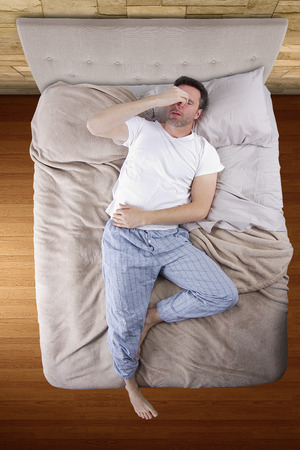 top view of bedroom with insomniac man unable to sleep
