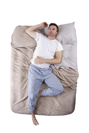 top view of sleep deprived man on a bed