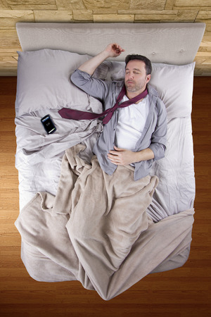 businessman sleeping in his work clothes with cellphone alarm clock Banque d'images
