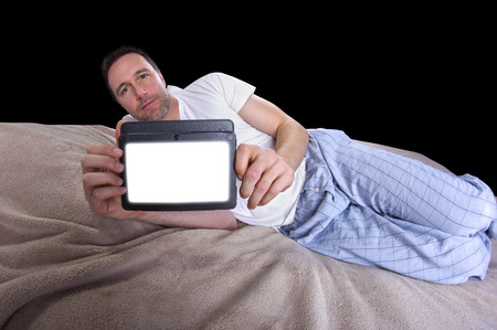 male reading on a tablet before going to sleep photo