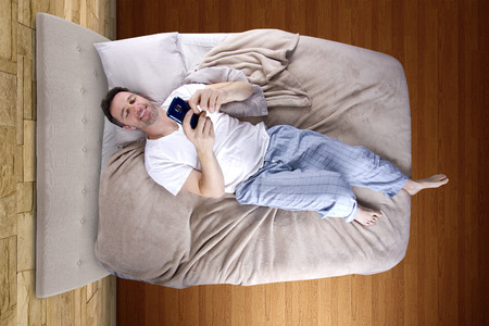 snoozing: man snoozing modern cell phone alarm clock Stock Photo