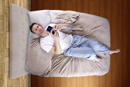 man snoozing modern cell phone alarm clock photo